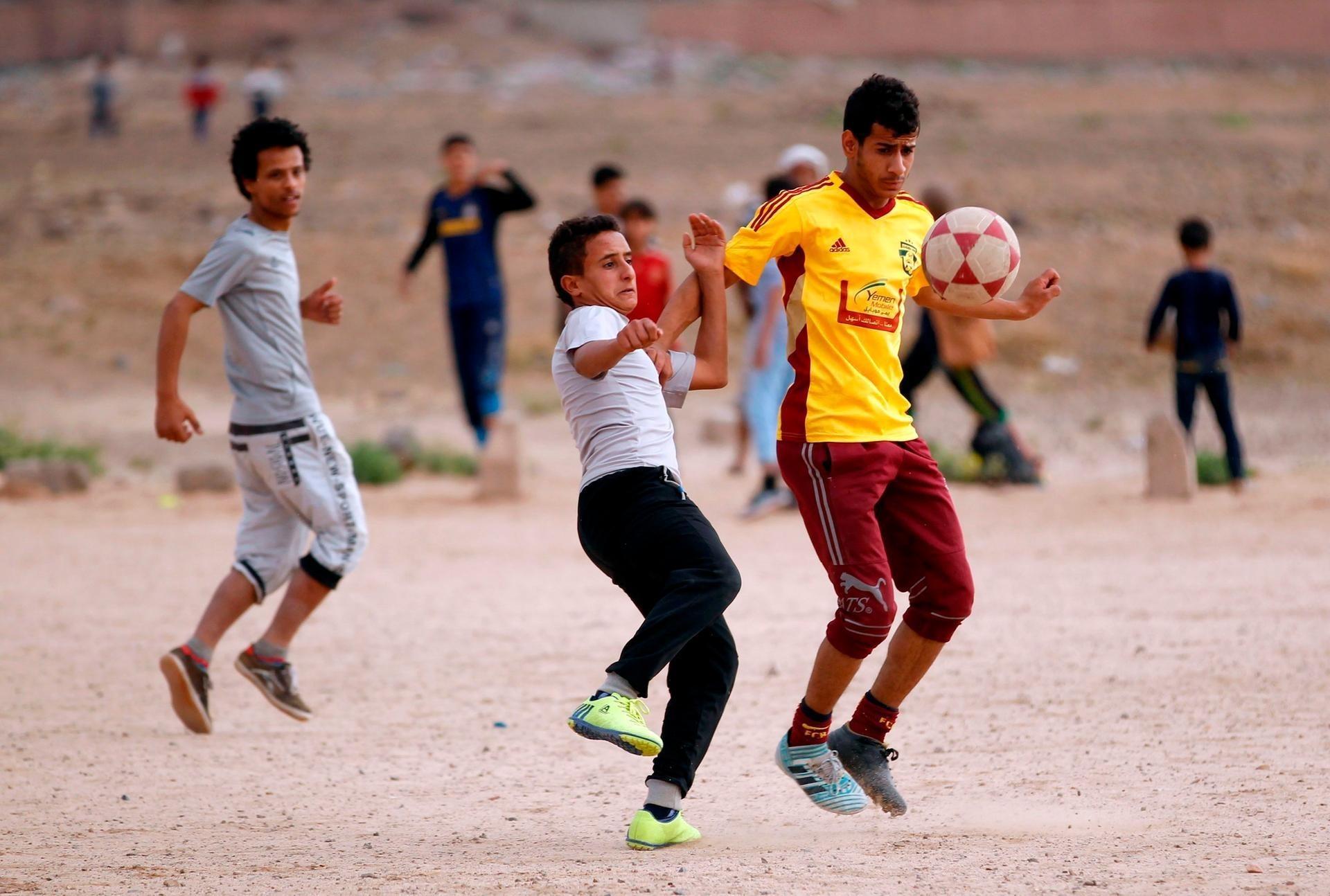 Yemeni youth take part in a football match in their neighbourhood in Sanaa.