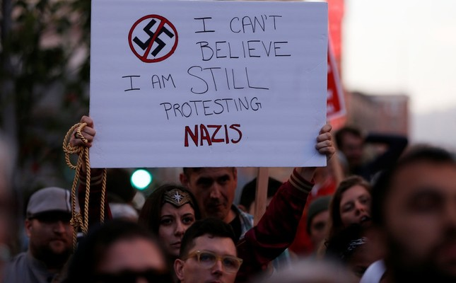 A demonstrator holds a sign during a protest in response to the Charlottesville car attack on counter-protesters after the Unite the Right rally organized by white supremacists, Oakland, California, Aug. 12.