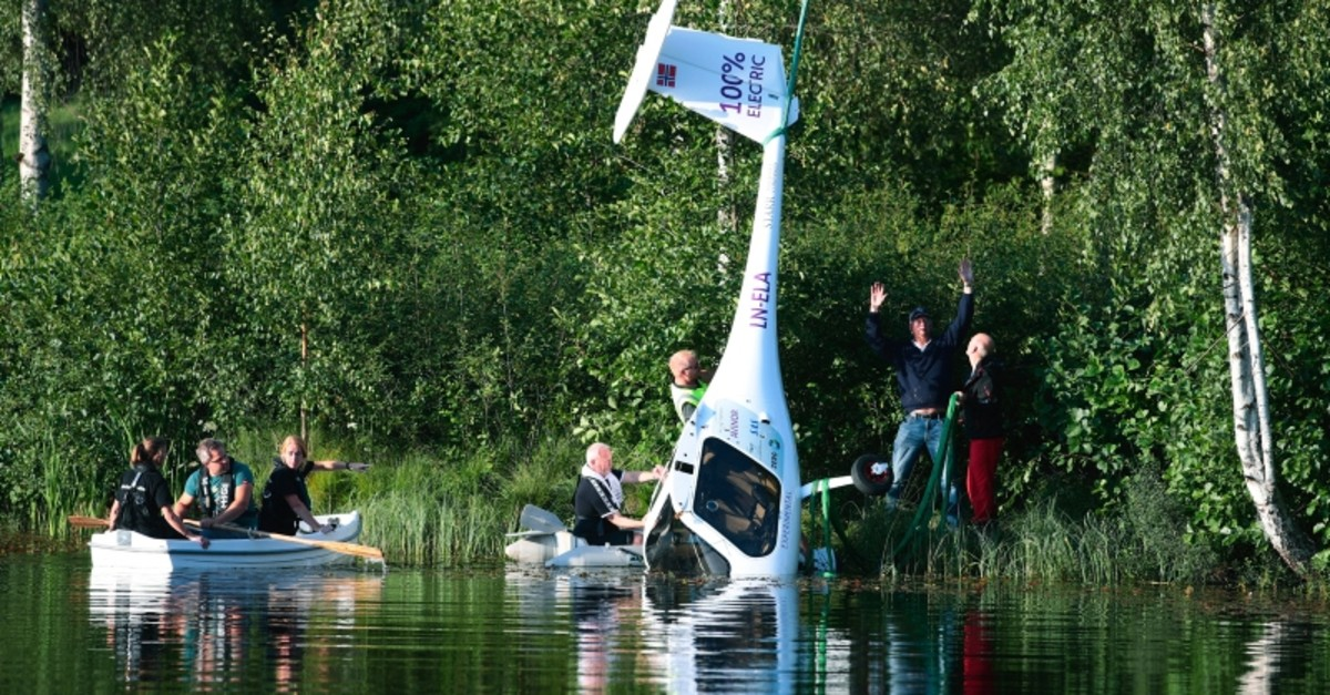 People lift an Avinor electric aircraft, a Pipistrel Alpha Electro out of the water, after it made an emergency landing, in Arendel, Norway, Wednesday, Aug. 14, 2019 (AP Photo(