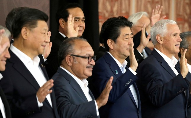 From left, Chinese President Xi Jinping, Papua New Guinea's PM Peter O'Neill, Japanese PM Shinzo Abe, and U.S. Vice President Mike Pence wave as they pose for a group photo at APEC Haus in Port Moresby, Papua New Guinea, Nov. 18, 2018. (AP Photo)