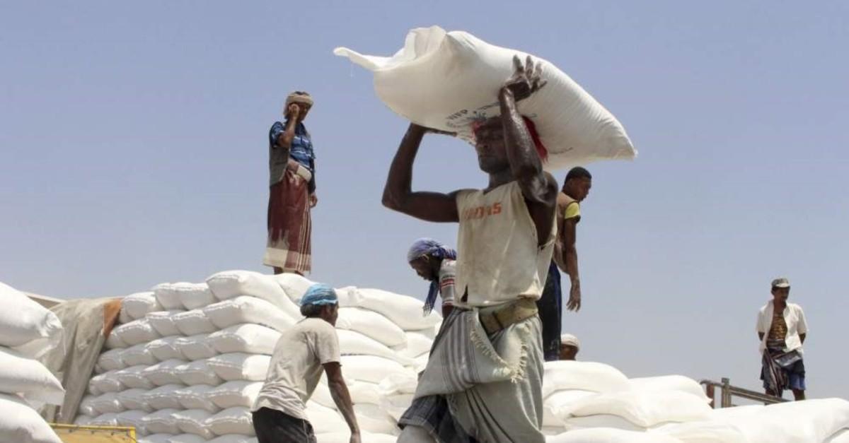 Men deliver U.N. World Food Programme (WFP) aid in Aslam, Hajjah, Yemen, Sept. 21, 2018. (Associated Press Photo)