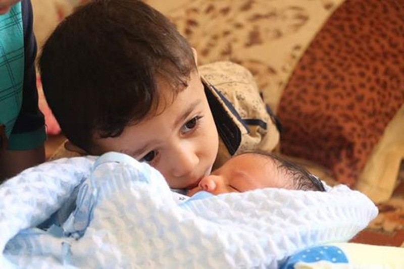 Waleed's older brother Mutasim, who survived a collapsing building in his dying mother's arms during Israeli attack in 2014, kisses his baby brother