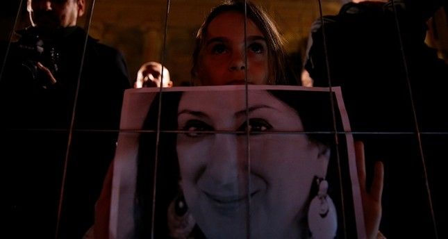 Girl holds photo of assassinated journalist Daphne Caruana Galizia near the newly rebuilt makeshift memorial during vigil to mark 13 months since her murder, in Valletta, Malta, Nov. 16, 2018. (Reuters Photo)