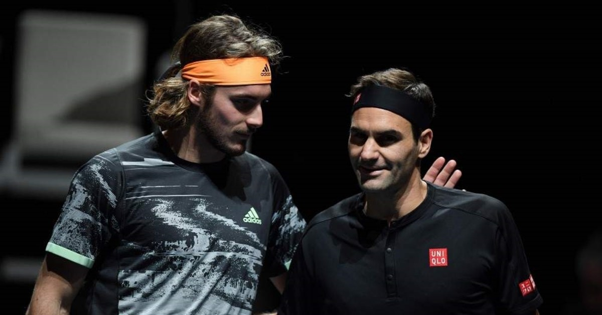 Tsitsipas (L) and Federer interact before the men's singles semi-final match on day seven of the ATP World Tour Finals in London on November 16, 2019. (AFP Photo)