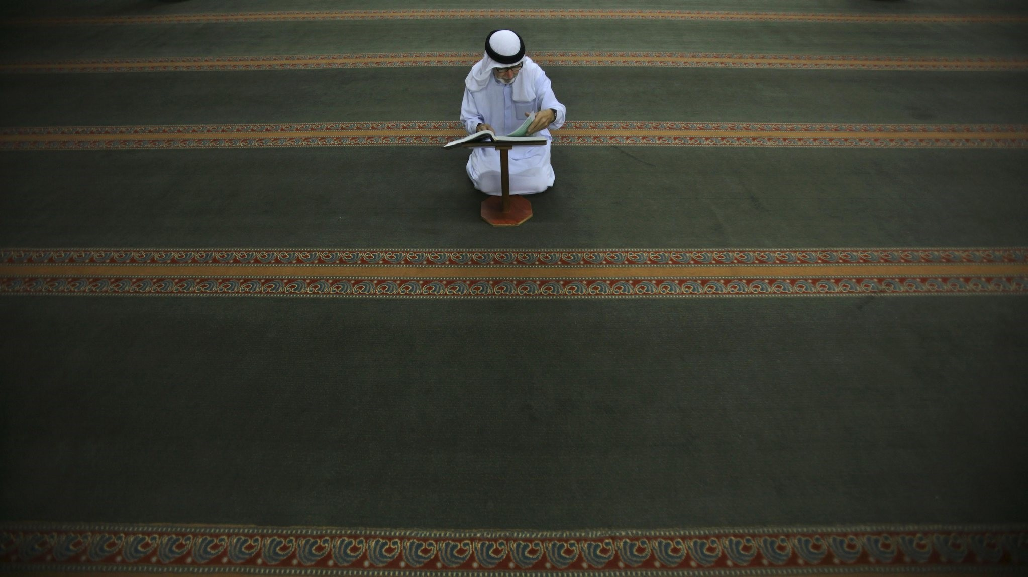 An elderly Palestinian Muslim man reads the Quran following the early morning prayer on the last day of the holy month of Ramadan at a mosque in West Bank, Ramallah, Sept. 9, 2010.
