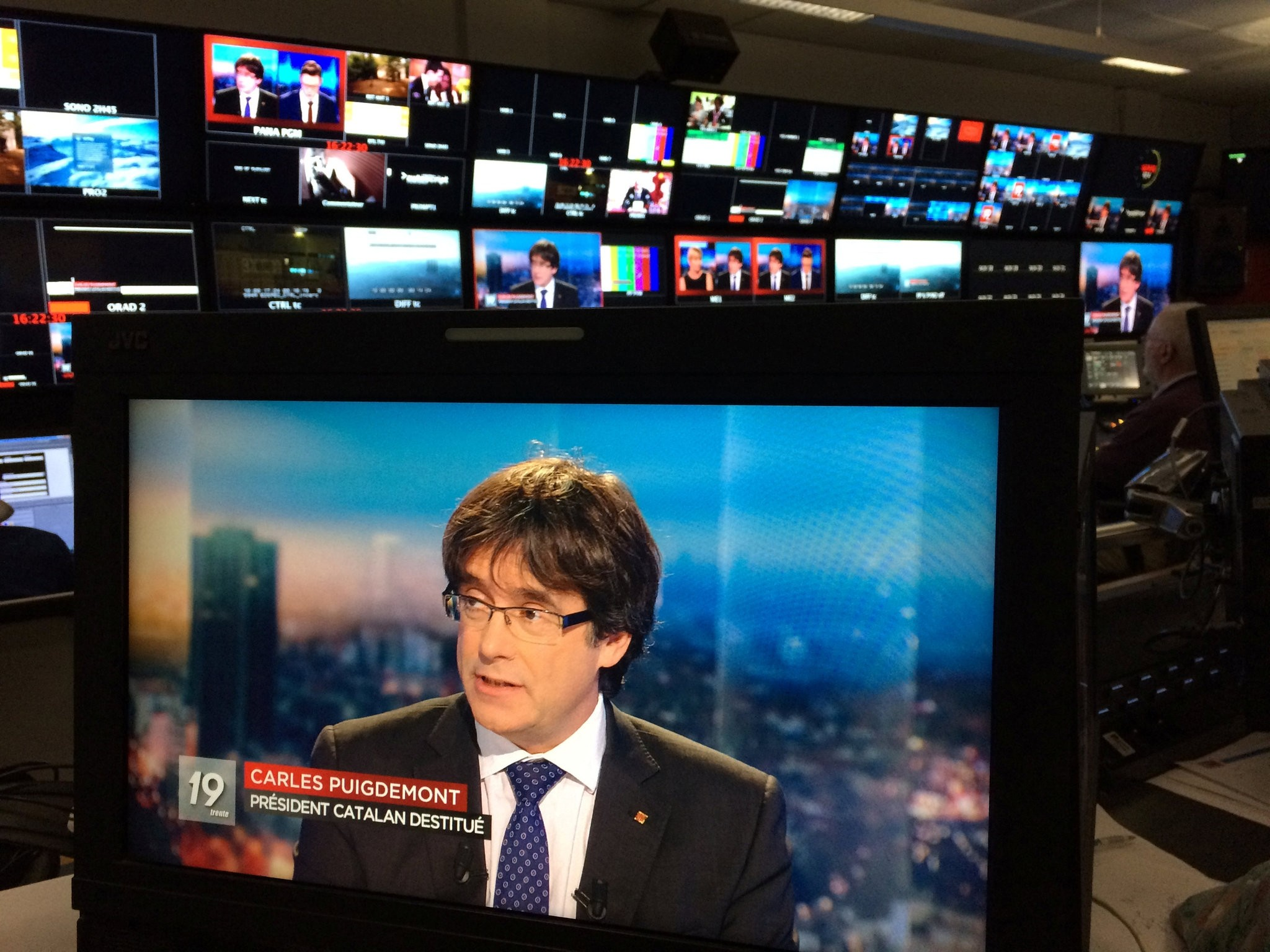 Ousted Catalan President Carles Puigdemont, who fled Belgium following the detention of eight Catalan ministers, appears on a monitor during a live TV interview on a screen in a bar in Brussels, Nov. 3.