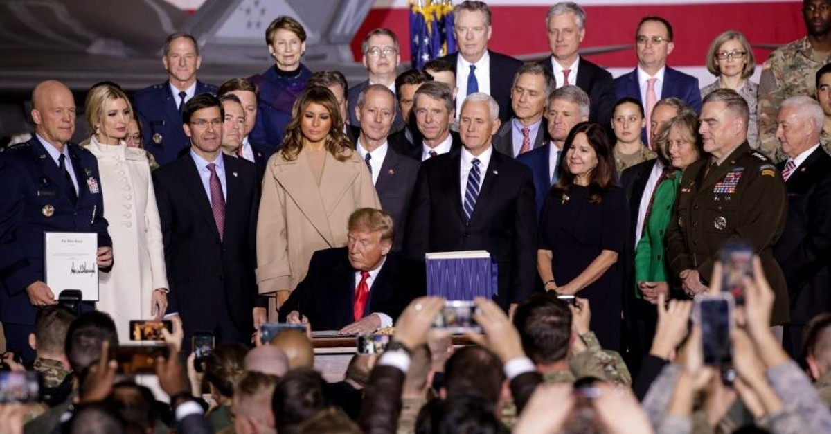 Encircled by top officials of his administration, US President Donald Trump signs $738 billion 2020 National Defense Authorization Act (NDAA) at Joint Andrews Base in Maryland, on Dec. 20, 2019. (AA Photo)