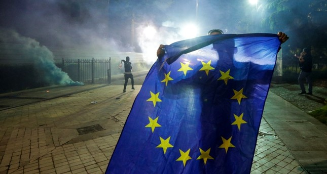 An opposition supporter holds an EU Flag outside Parliament building during an anti-government protest, calling on Prime Minister Edi Rama to step down, in Tirana, Albania, June 8, 2019. (REUTERS Photo)