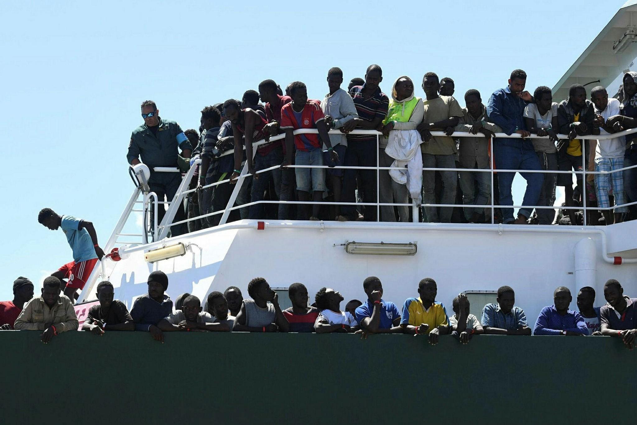 Migrants wait to disembark from the Spanish ship 'Rio Segura' in the harbor of Salerno, Italy, June 29.