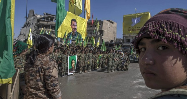 Terrorists from the Women's Protection Units (YPJ), the women's branch of the YPG, that recruits children, celebrate their so-called victory holding a flag bearing the photo of PKK leader Abdullah Öcalan in Raqqa, Syria in October 2017.
