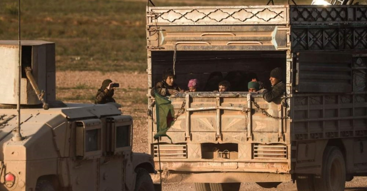People evacuated from Daesh's embattled holdout of Baghouz sit in the back of a truck, Feb. 25, 2019. (AFP)