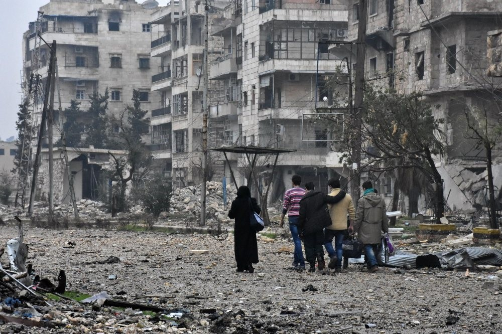 Syrian residents leave Aleppo's Bustan al-Qasr neighborhood following a clash between regime and opposition groups, Dec. 13, 2016.Photograph by AFP