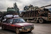 سيارة مدنية تقل نازحين في إدلب بجانب آليات تحمل تعزيزات عسكرية للجيش التركي