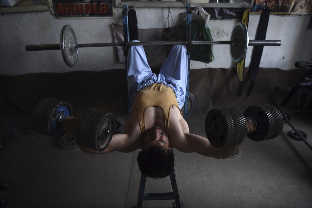 An Afghan bodybuilder exercises using dumbbells made from spare car parts.