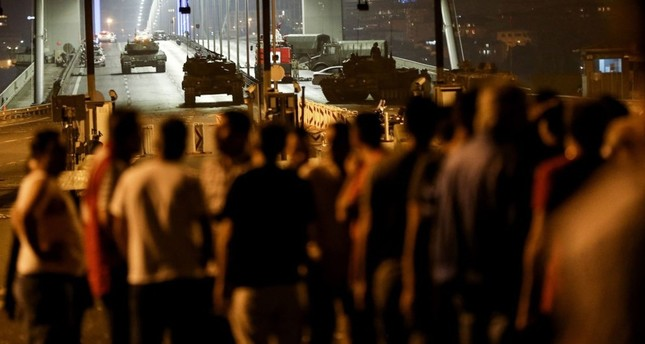 An anti-coup crowd looks at tanks and putschist soldiers on an Istanbul bridge where 34 people were killed on July 15, 2016.