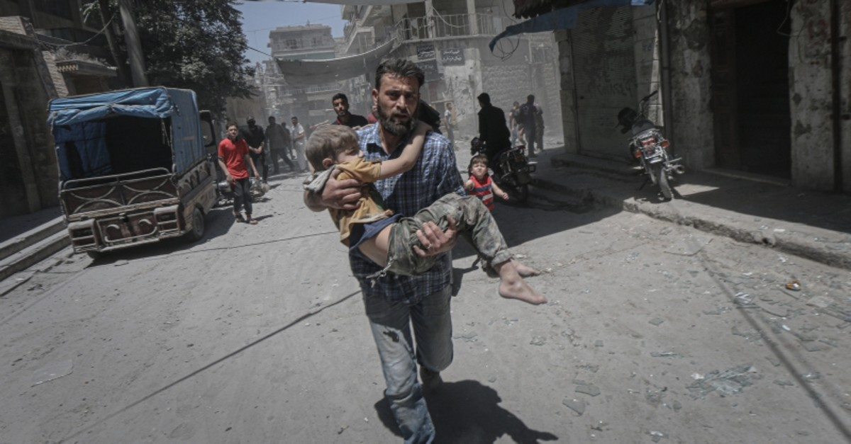 A man flees while carrying a child in northwest Syria's Idlib during Assad regime's air strikes, May 27, 2019. (AA Photo)