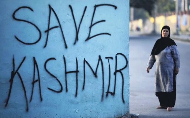A Kashmiri woman stands next to graffiti written on a wall in Srinagar, Kashmir, Sept. 15, 2019.