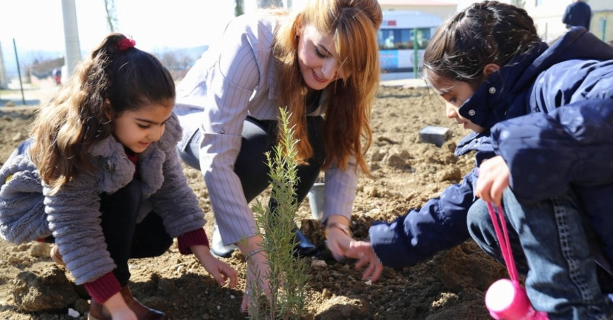 A woman helps two children plant a tree in Diyarbaku0131r, Feb. 19, 2018. Turkey regularly holds afforestation drives to increase the number of trees.