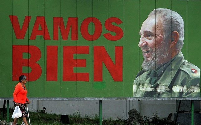 This file photo taken on November 21, 2006 shows a woman walking past a bilboard of Cuban President Fidel Castro ('We're On The Good Track') 21 November 2006, in Havana. (AFP Photo)