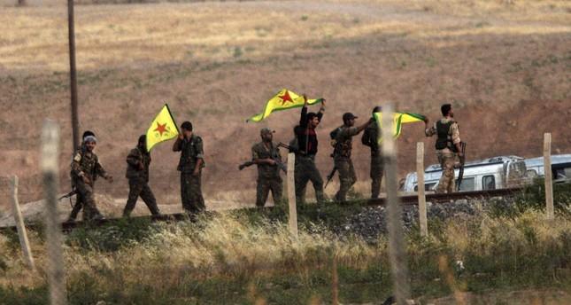 YPG terrorists hold flags near the Akçakale border gate between Turkey and Syria, Şanlıurfa, June 15, 2015.