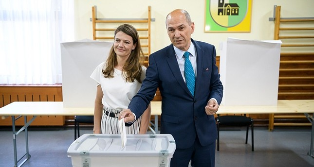 Janez Jansa R, former Slovenian Prime Minister and President of Slovenian Democratic Party SDS, flanked by his wife Urska Bacovnik L, casts his ballot at a polling station in a small village Sentilj, Slovenia, on June 3, 2018. AFP Photo