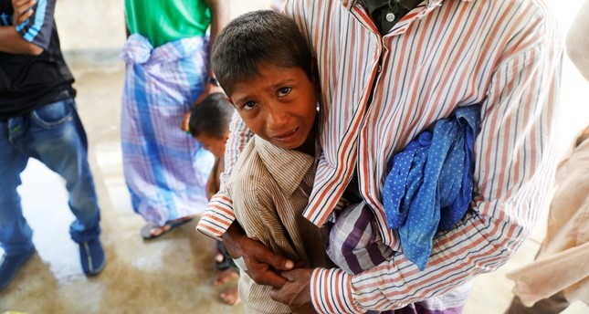 Lalu Miya hugs his surviving son as he cries over the bodies of his wife and children, who died after a boat carrying Rohingya refugees capsized.