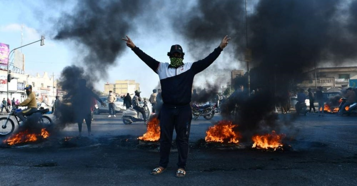 An Iraqi anti-government demonstrator gestures next to burning tyres in the southern Iraqi city of Nasiriyah, Feb. 10, 2020. (AFP Photo)