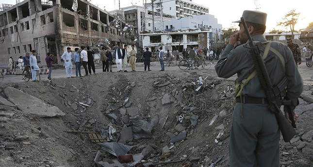 In this Wednesday, May 31, 2017 file photo, security forces stand next to a crater created by a massive explosion, that killed over 150 according to the Afghan president, in front of the German Embassy in Kabul, Afghanistan. (AP Photo)