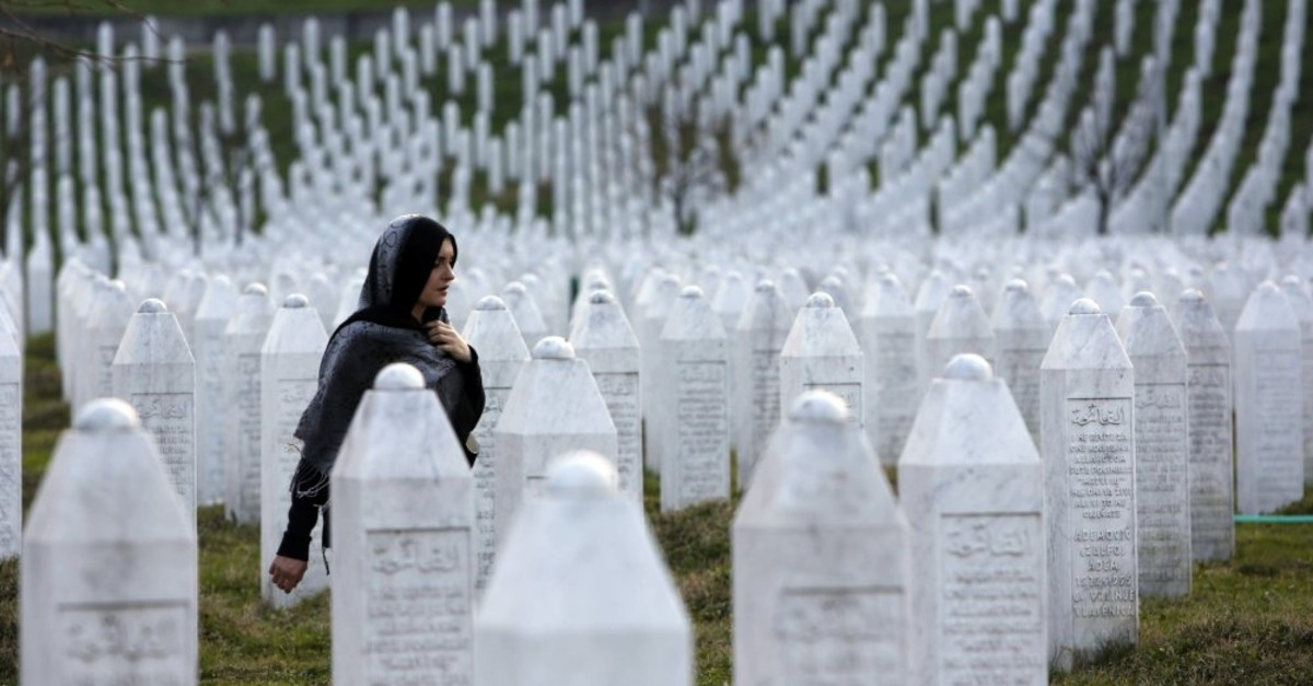 A Bosnian woman walks among gravestones at the genocide memorial center in Potocari near Srebrenica, March 26, 2019.