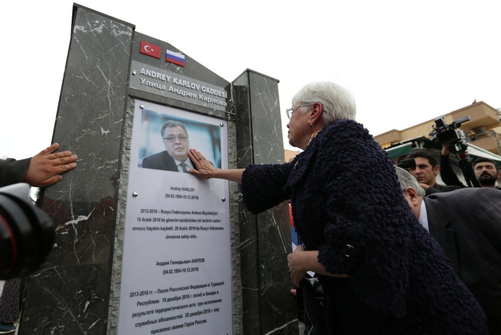Marina Karlova, the widow of Andrey Karlov, touches the late ambassador's photo on a memorial unveiled in Antalya, March 22.