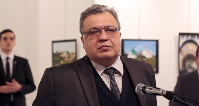 This file photo shows Andrei Karlov, late Russian ambassador to Turkey, speaking at a gallery in Ankara on Dec. 19, 2016, shortly before a gunman, seen at the rear on the left and posing as a bodyguard, shot him dead. AP Photo