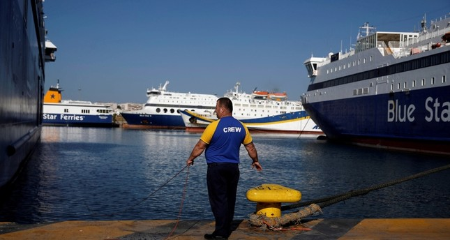A seaman holds a rope next to a moored passenger ferry during a second consecutive 24-hour strike of Greece's seamen's federation PNO against austerity policies affecting their sector, at the port of Piraeus, Greece, Sept. 4, 2018. (Reuters Photo)