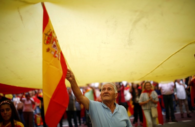 An elderly man waves a Spanish flag as he marches with during Spain's National Day celebrations in the Catalan city of Barcelona, Spain, Friday, Oct. 12, 2018. (AP Photo)