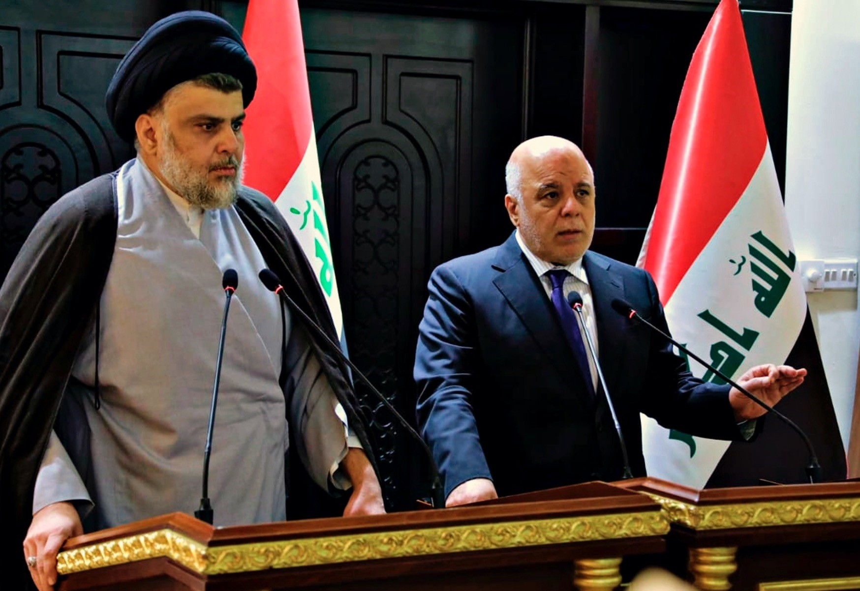 Shiite cleric Muqtada al-Sadr (L) and Iraqi Prime Minister Haider al-Abadi hold a press conference in the heavily fortified Green Zone in Baghdad, May 20.