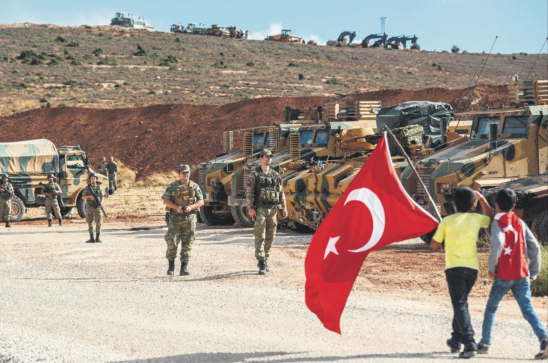 Turkish soldiers stand near armored vehicles as two young boys holding Turkish flags arrive during a demonstration in support of the Turkish armyu2019s Idlib offensive along the Turkey-Syria border near Reyhanlu0131, Hatay, Oct. 10, 2017.