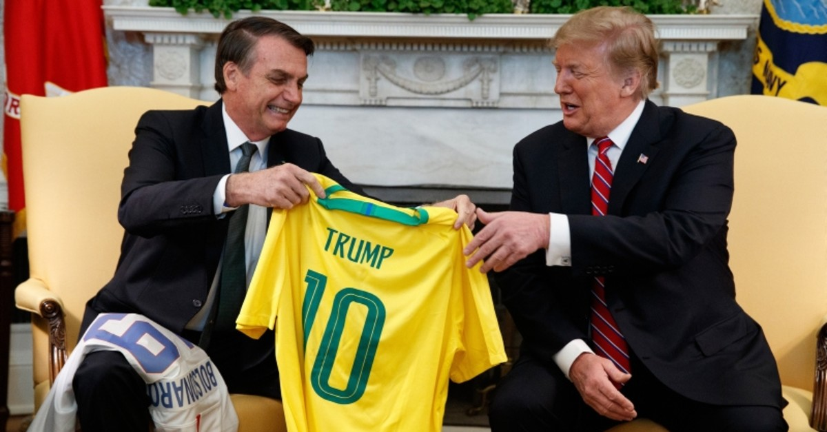 Brazilian President Jair Bolsonaro presents President Donald Trump with a Brazilian national team soccer jersey in the Oval Office of the White House, Tuesday, March 19, 2019, in Washington. (AP Photo)