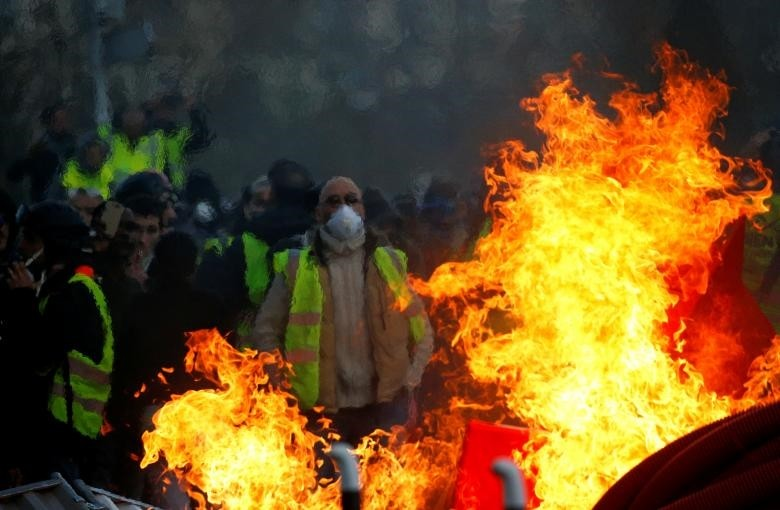 Protesters wearing yellow vests are seen behind a fire as they attend a demonstration of the ,yellow vests, movement in Angers. (Reuters Photo)