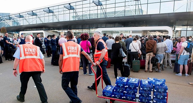 Firemen distribute water to waiting passengers after a power outage at Brussels Airport, in Zaventem, on June 15, 2017. (AFP Photo)