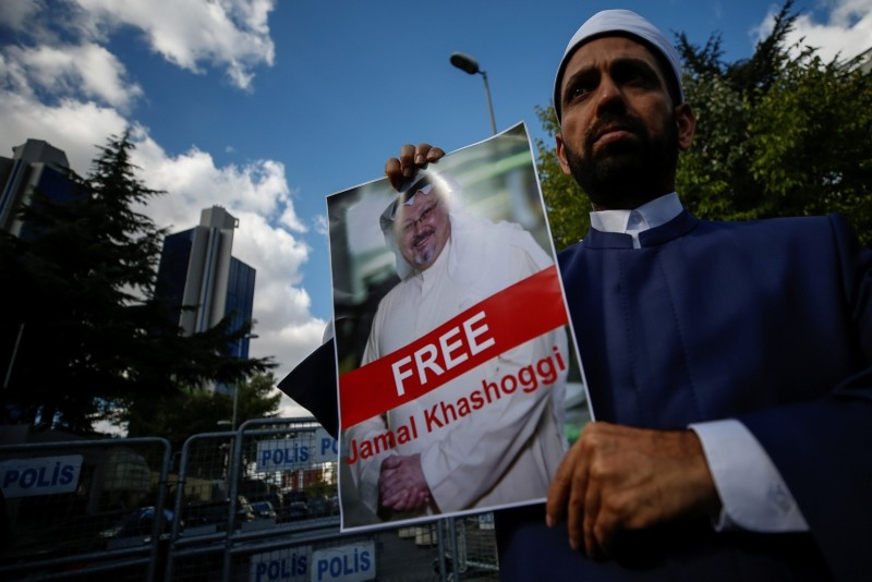 Holding a poster of missing Saudi writer Jamal Khashoggi, a man stands near the Saudi Arabia consulate in Istanbul, Friday, Oct. 5, 2018. (AP Photo)