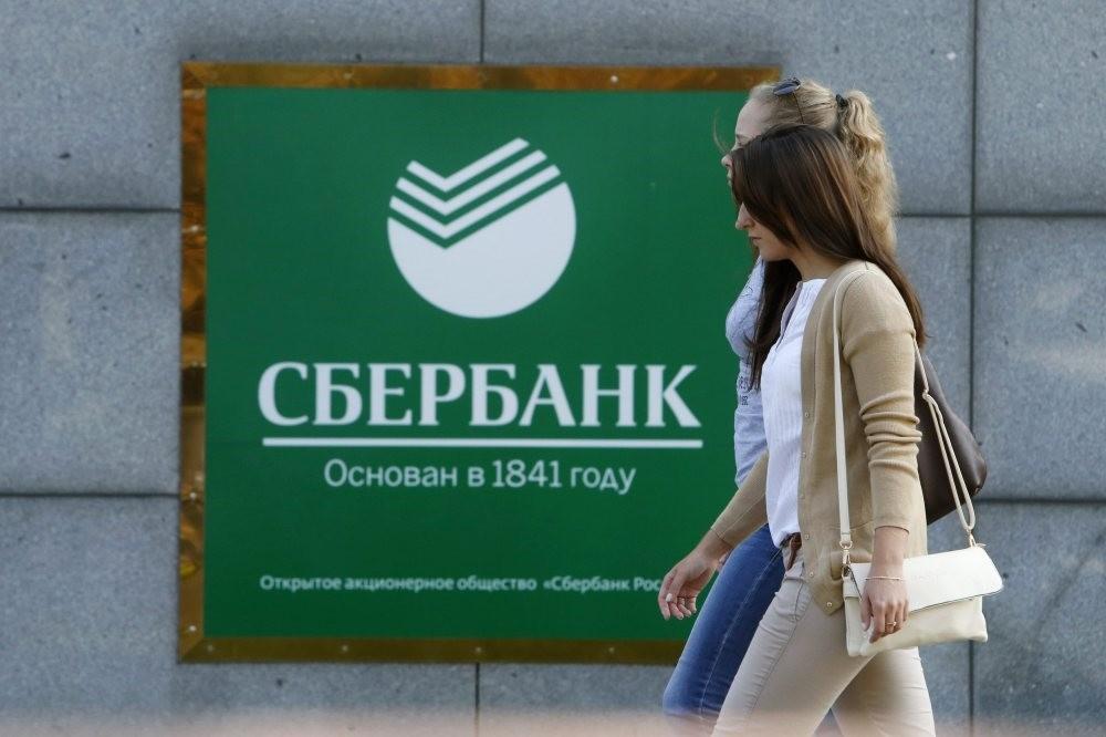 Women walk past an office of Sberbank in Moscow.