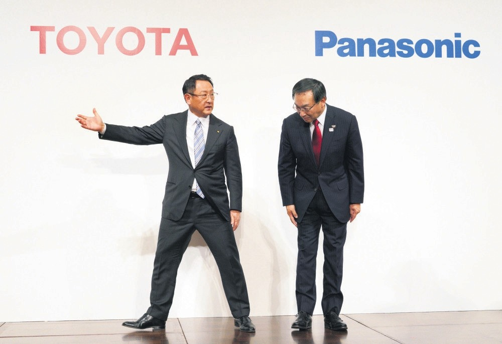 Toyota Motor Corporation President Akio Toyoda (L) escorts Panasonic Corporation President Kazuhiro Tsuga after a joint press conference yesterday in Tokyo.