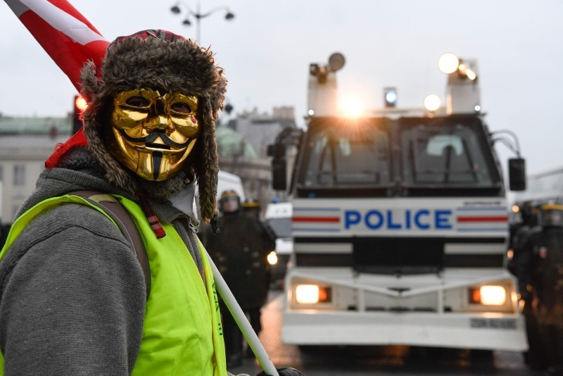 A masked protestor stands in front of a police vehicle in Paris on January 5, 2019, during a rally by yellow vest ,Gilets Jaunes, anti-government protestors. (AFP Photo)
