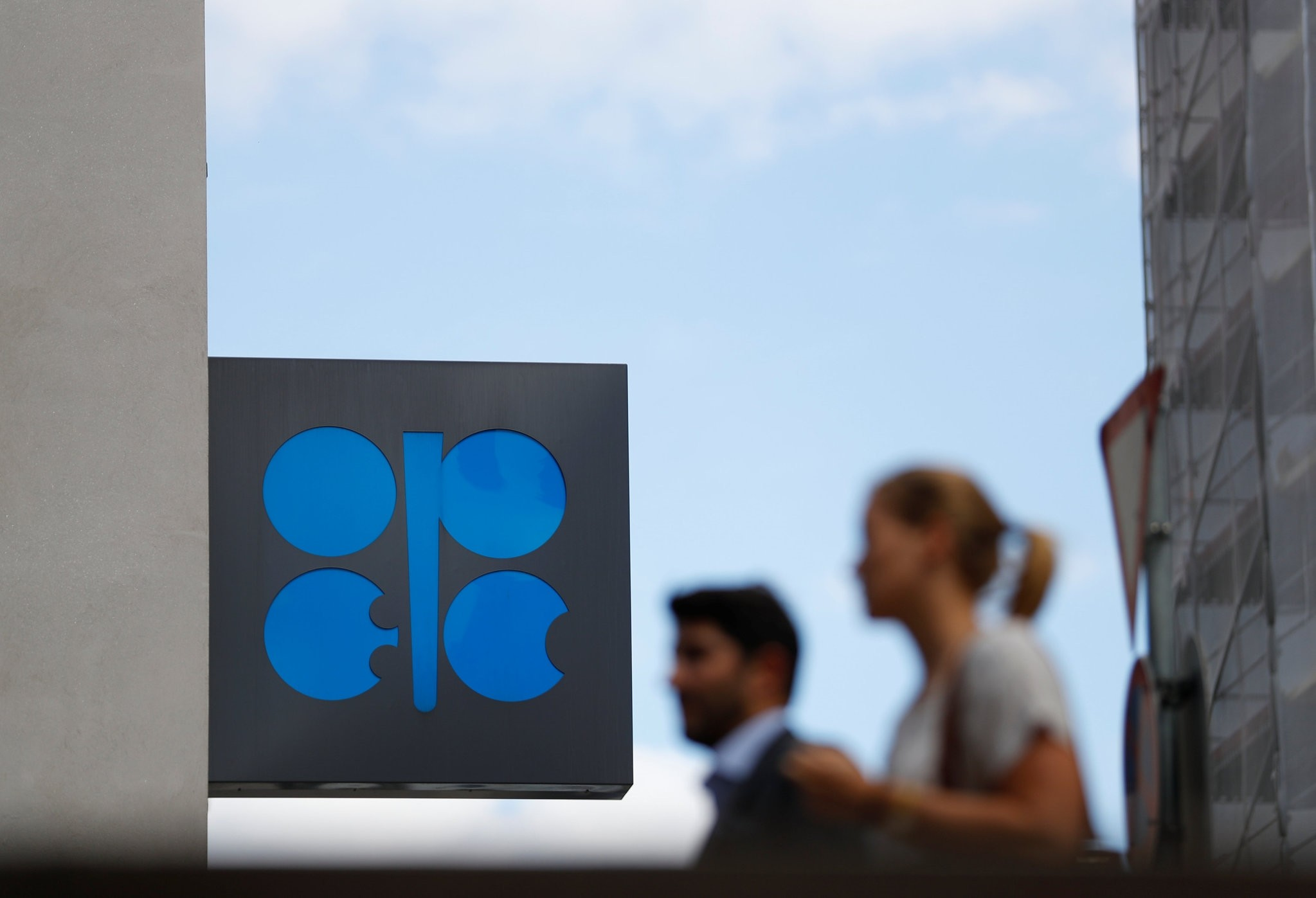 People pass the logo of the Organization of the Petroleum Exporting Countries (OPEC) in front of OPECu2019s headquarters in Vienna, Austria, June 19.