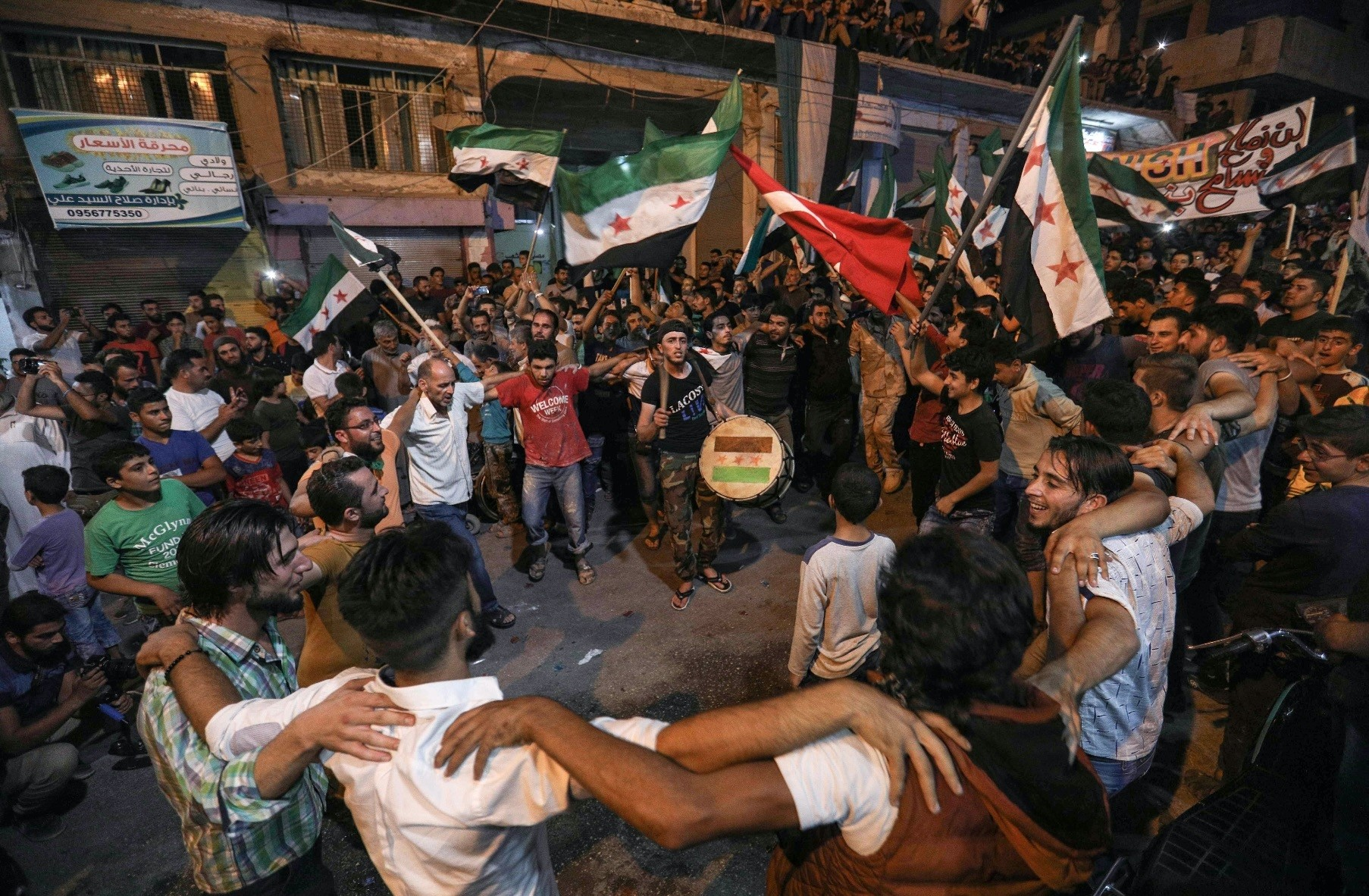Syrians dance, chant slogans and strike drums while others wave Syrian opposition and Turkish flags during a demonstration in Binnish in northern Idlib province, Sept. 17