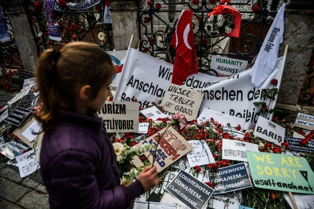 A child stands in front of a makeshift memorial with flowers and candles in tribute to victims at the site of the Jan. 12 deadly terrorist attack in Istanbul's tourist hub of Sultanahmet, Jan. 14, 2016.