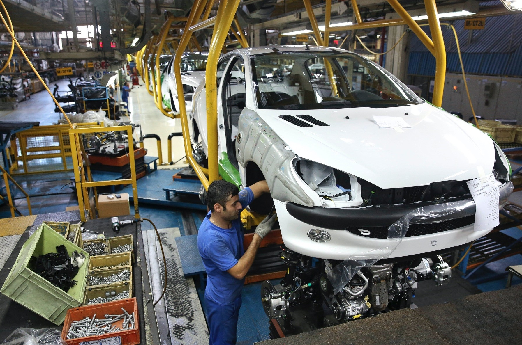 An Iranian worker assembles a Peugeot 206 at the state-run Iran-Khodro automobile manufacturing plant, Tehran, Iran.