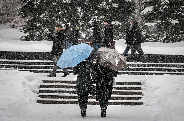 People walk with umbrellas during a snowfall in central Moscow, Russia, Feb. 3, 2018. (AFP Photo)