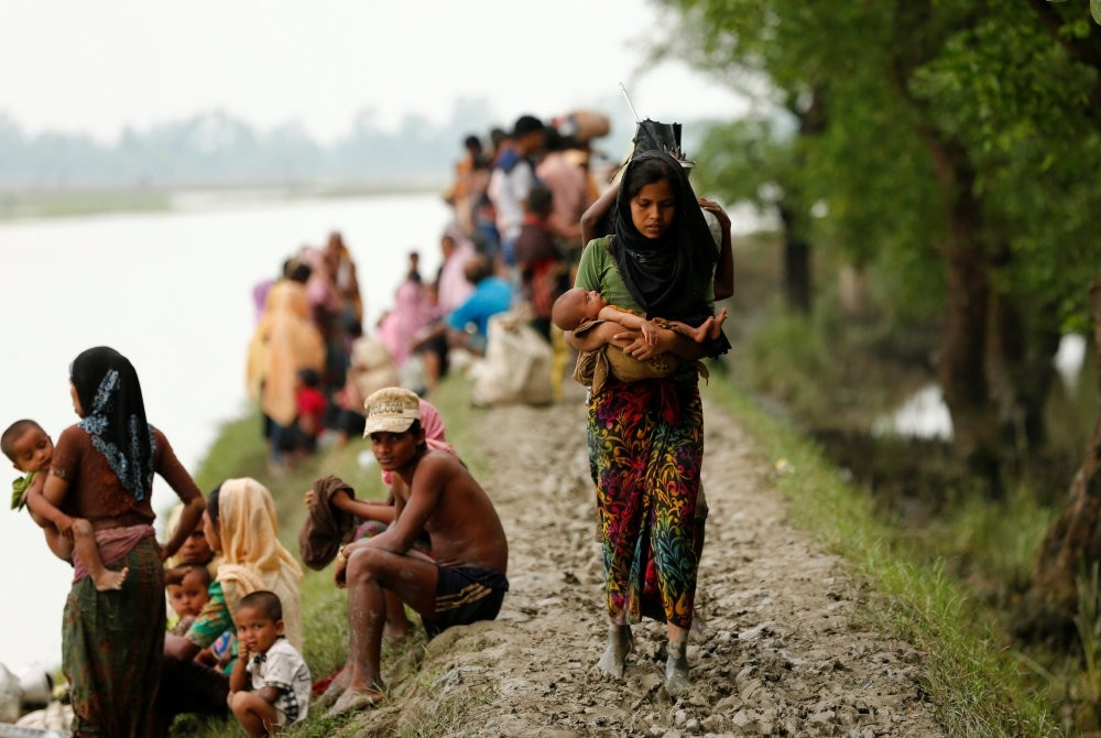 A Rohingya refugee woman with her child walks on a muddy path after crossing the Bangladesh-Myanmar border in Teknaf, Bangladesh, Sept. 7.