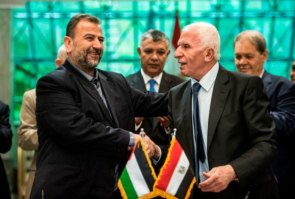 Head of the Hamas delegation, Saleh Arouri (L), and Fatah leader Azzam Ahmad shake hands after signing a reconciliation deal, Cairo, Oct. 12.