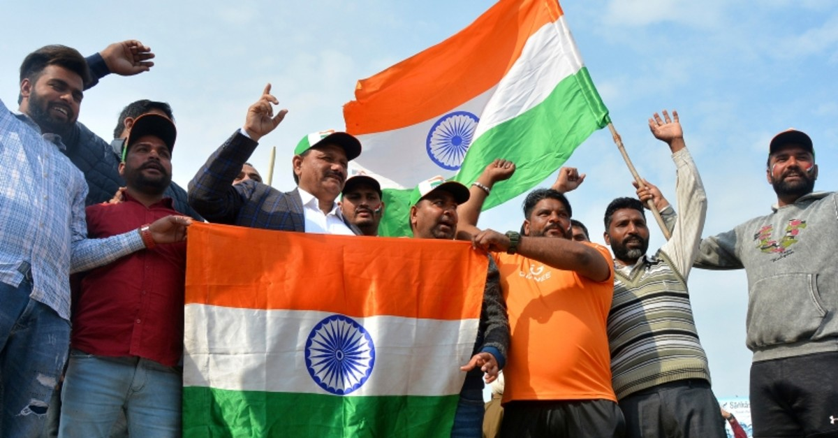 Indians hold national flags and shout slogan as they wait to welcome Indian pilot at India Pakistan border at Wagah, India, Friday, March 1, 2019. (AP Photo)
